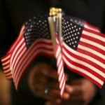 A woman holds a cluster of U.S. flags during a U.S. Citizenship and Immigration Services naturalization ceremony in Oakland